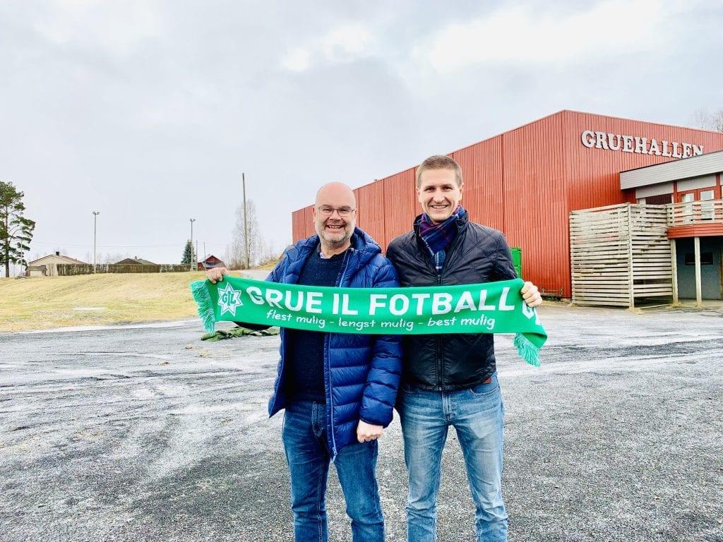 KLARE: Gjermund Holt og Rune Skasberg i prosjektgruppa. Bak dem og ved siden av Gruehallen til høyre kan det stå klar en flerbrukshall høsten 2021. Foto: Liv Rønnaug B. Lilleåsen