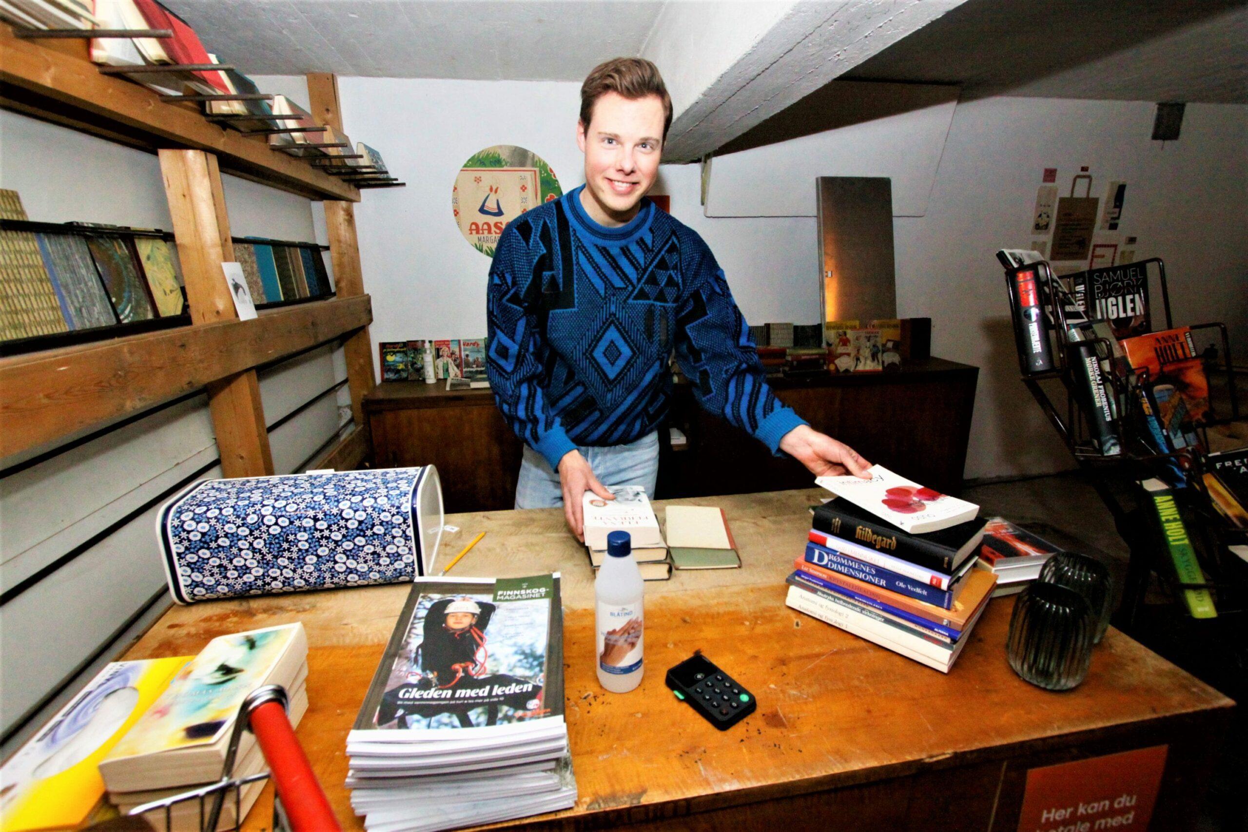 STORTRIVES: Andreas Søvik Helgeberg flyttet tilbake til Svullrya i juni 2019, og sier han stortrives. Her er han bak disken i sitt nyåpnede bokhandleri. Foto: Liv Rønnaug B. Lilleåsen