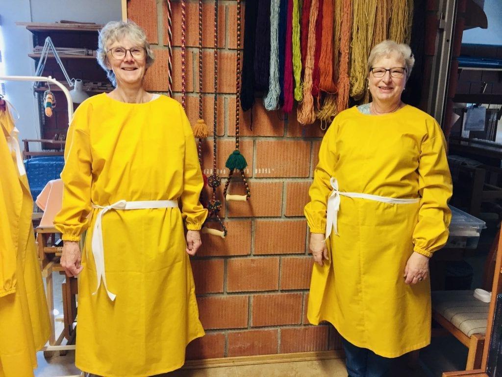 I GANG: Grue Husflidslag er godt i gang med dugnaden. Her er Solveig Søråsen (t.v.) og Ella Rismoen i to påskegule smittevernfrakker. Foto: Grue Husflidslag