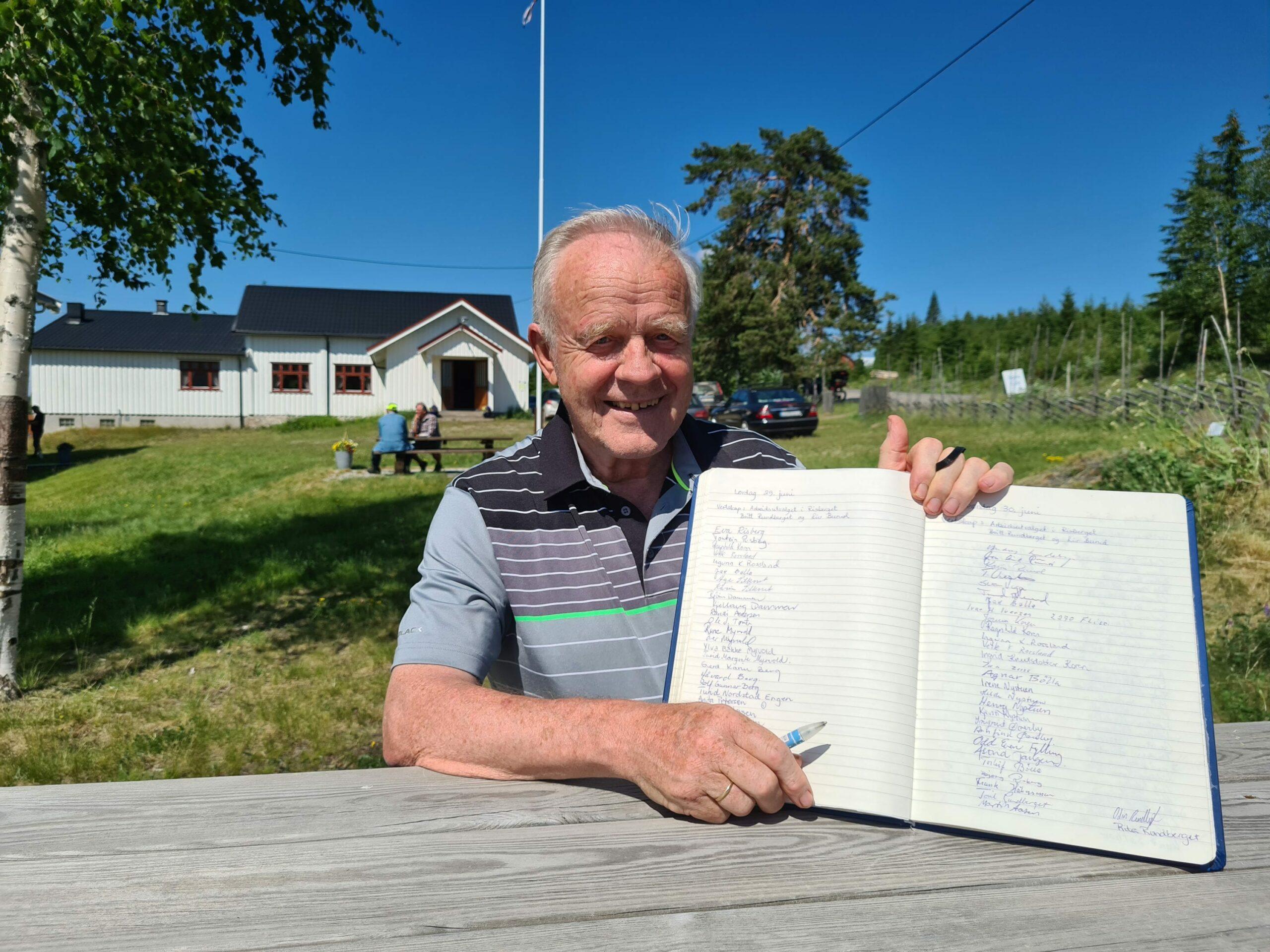 HENTER UNDERSKRIFTER: Alle som besøker sommerkafeen i Risberget må skrive seg inn i gjesteboka. Torleif Bølla sørger for at ingen «slipper unna». Sommerkafeen er åpen hver lørdag og søndag gjennom hele skoleferien.